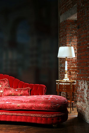table lamp with white lamp shade adjoining a red sofa